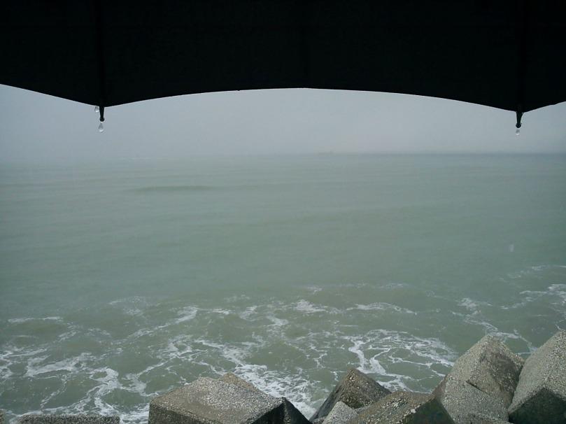 Imagen de un paraguas negro junto al mar